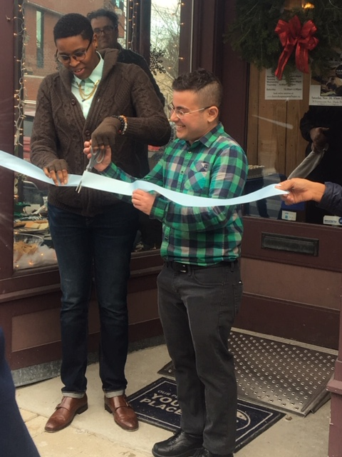 Tj and Ren laugh as they hold scissors and cut ribbon
