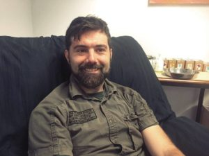 Andrew Cheever sits in a chair and smiles. He is a white man with short brown hair and a trim brown beard.
