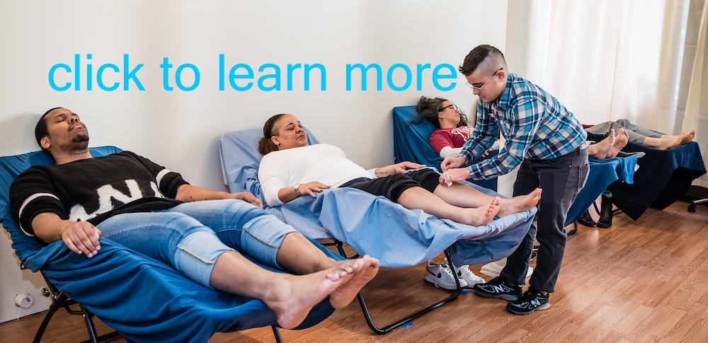 Click to learn more blue text on wall in photo showing Oren Ren Pilinger Licensed Acupuncturist treating someone in a recliner while other people relax on other recliners in the treatment room at Boston Acupuncture Project in Hyde Park MA.