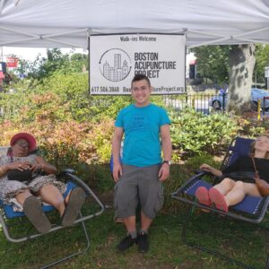 Ren stands between two people in recliners getting acupuncture in a pop up tent outdoors. Photo by Tj Johnson.