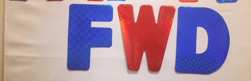 Big glittery letters say PAY IT FWD in alternating red and blue. Below this is a single alphanumeric code hand written in red marker on a piece of paper and attached to the wall with a push pin.